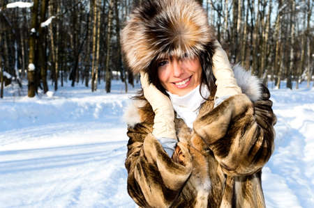 pretty smiling girl in fur coat in winter forest Stock Photo - 7587949