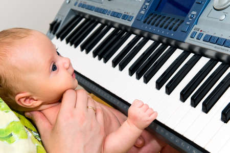 Baby playing the piano keyboard photo