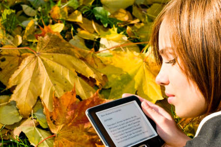 young woman reading Longfellow poetry in autumn park Stock Photo