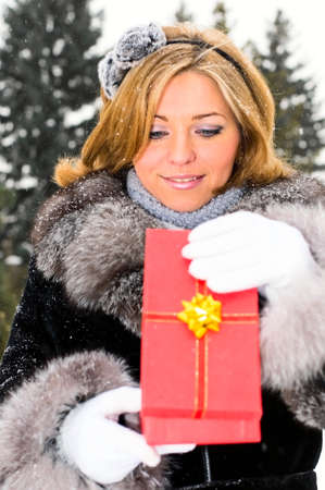 young smiling woman open a present  photo