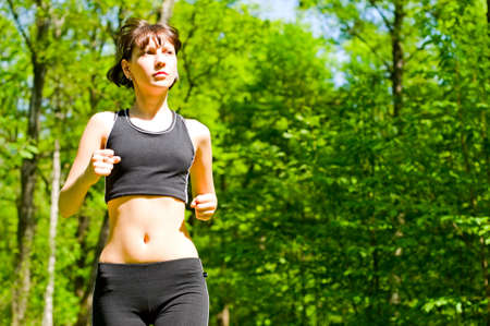 pretty girl jogging in summer forest