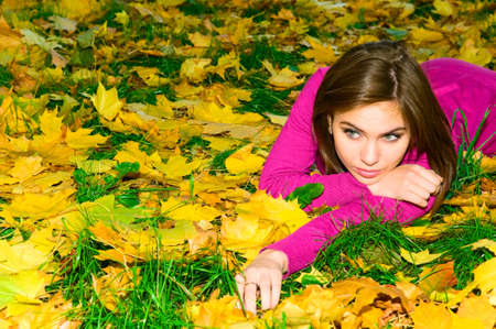lying in leaves: pretty caucasian girl in autumn forest