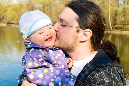 father kisses child on the cheek photo