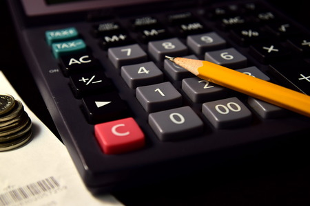 checkbook: Pencil and Calculator beside the Bill and Coins