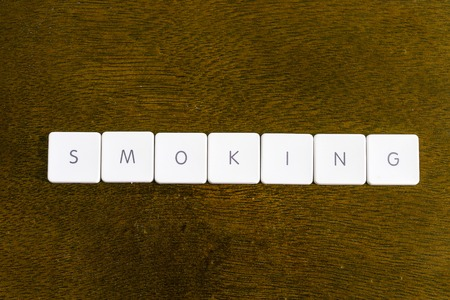 SMOKING word written on plastic keyboard alphabet with dark background