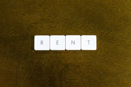 RENT word written on plastic keyboard alphabet with dark background