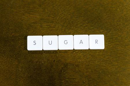 SUGAR word written on plastic keyboard alphabet with dark background