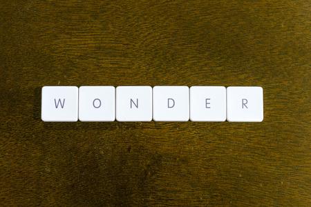 WONDER word written on plastic keyboard alphabet with dark background