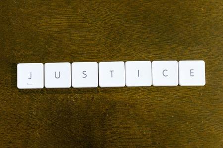 JUSTICE word written on plastic keyboard alphabet with dark background