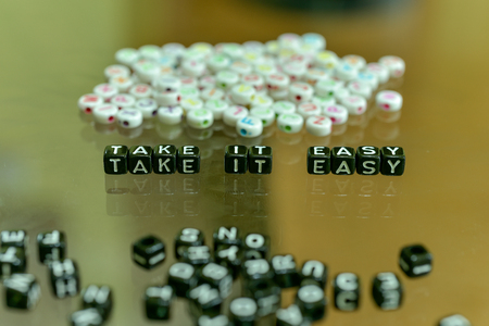 TAKE IT EASY  written with Acrylic Black cube with white Alphabet Beads on the Glass Background 免版税图像