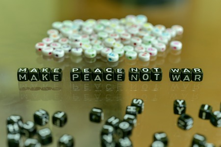 MAKE PEACE NOT WAR  written with Acrylic Black cube with white Alphabet Beads on the Glass Background