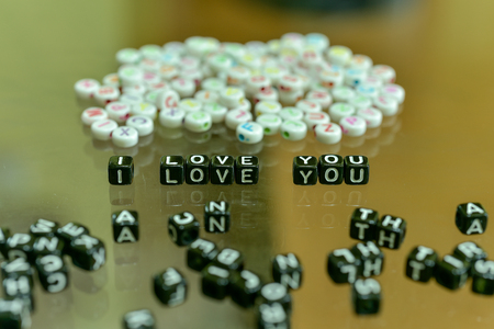 I LOVE YOU  written with Acrylic Black cube with white Alphabet Beads on the Glass Background 版權商用圖片
