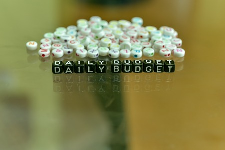 DAILY BODGET  written with Acrylic Black cube with white Alphabet Beads on the Glass Background