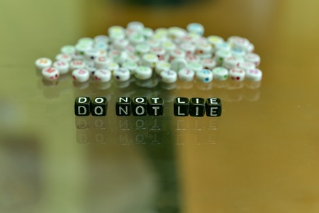 DO NOT LIE  written with Acrylic Black cube with white Alphabet Beads on the Glass Background