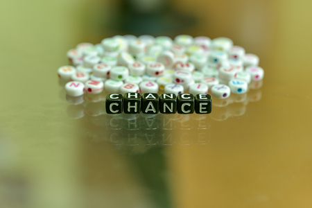 CHANCE written with Acrylic Black cube with white Alphabet Beads on the Glass Background
