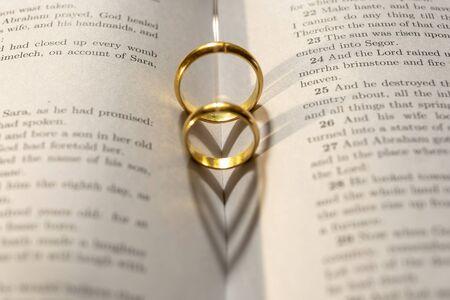 Zwei Eheringe auf der Bibel mit Schatten der Herzform auf der Seite Standard-Bild