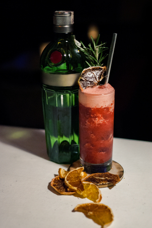 bartending: stwarberry red coctail with bottle of gin decorated with dry oranges and rosemary