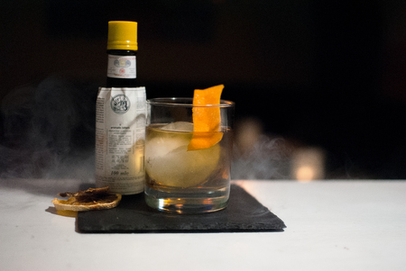 barmen: old fashioned cocktail with ice ball and smoke Stock Photo