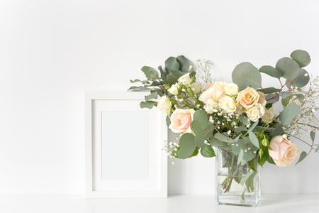 White fame mockup with peach, cream anf fresh greenery bouquet for wedding day