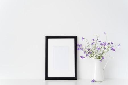 Black portrait frame mockup with wild flowers in vase near white wall. Empty frame mock up for presentation design. Template framing for modern art.