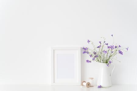 Makieta rama biały portret z dzikich kwiatów w słoiku i jedwabne wstążki w pobliżu białej ściany. Pusta rama makieta do projektowania prezentacji. Oprawa szablonu dla sztuki współczesnej.