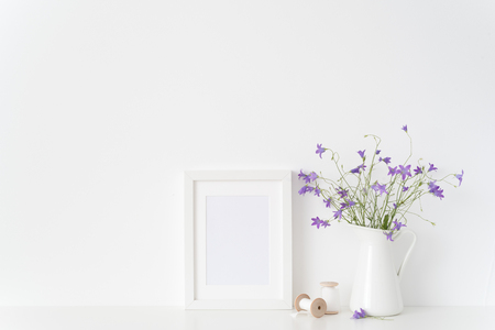 White portrait frame mockup with wild flowers in jar and silk ribbons near white wall. Empty frame mock up for presentation design. Template framing for modern art. Banque d'images
