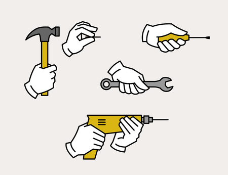 Hand holding drill, spanner, screwdriver, hammer and nail. Hardware tools.