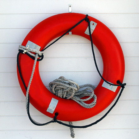Photo of an orange life preserver with rope on a white board background Фото со стока