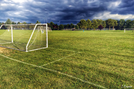 Soccer Net on a green field with storm clouds overhead