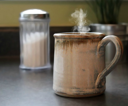Photo of a cup of hot coffee with steam coming out of the cup, sitting on a counter top Stock Photo