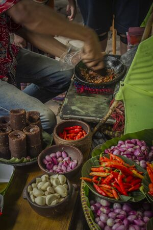 The seller is making special sambal for traditional fried tofu
