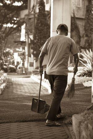 A cleaner sweeps the dry leaves outside the building