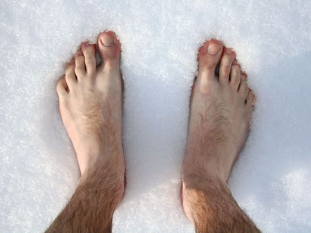 Naked feet in snow. top view.