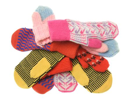 seasonal clothes: heap of different motley wool mittens isolated on white background