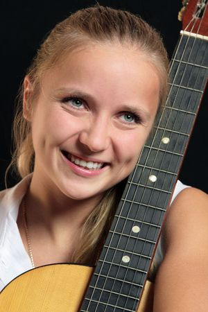 young smiling woman with guitar over black background Stock Photo - 8106334