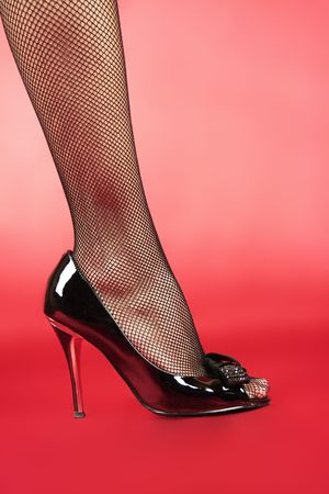 slender woman foot in black glossy shoe isolated on red background
