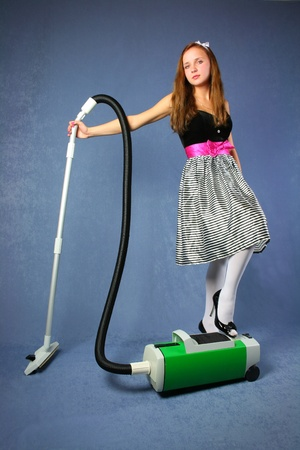 Young cute woman in bright dress with hoover stands over blue background