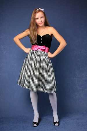 Young cute woman in bright dress stands over blue background photo