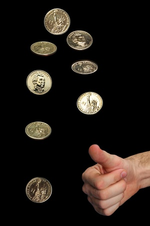 coin toss: isolated mans hand and thrown golden dollar coin in differennt phases of spinning. The background is black.