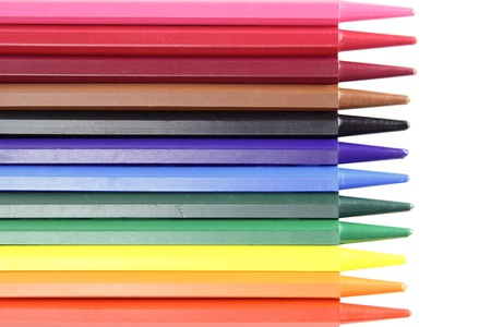 twelve color crayons lie over white background photo
