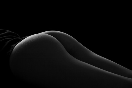 Black and white image of female buttocks on black bacground Stock Photo