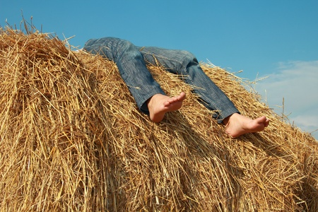 young girl lies on roll of dry hay under clear sky. bottom view. photo