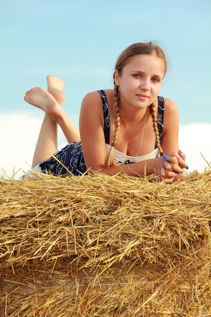 innocent girl: Young attractive barefoot girl lying on a bale of yellow straw Stock Photo