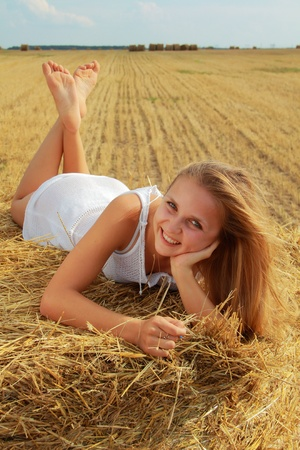 barefoot people: young smiling caucasian girl in white transparent dress lies on bale of straw Stock Photo
