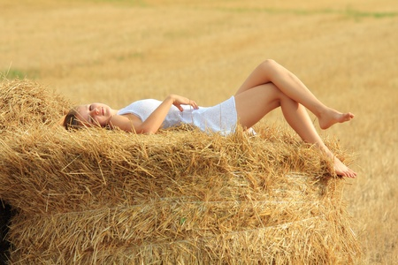 Young attractive barefoot girl lying on a bale of yellow straw at field