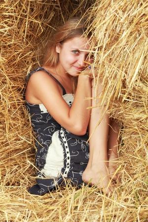 linda chica sonriente en sarafan sentarse entre las pacas de paja Foto de archivo - 10788276