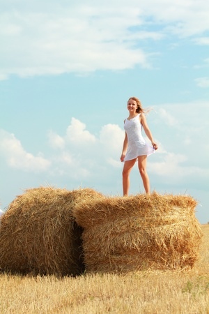 transparent dress: young caucasian girl in white transparent dress dancing on bale of straw Stock Photo