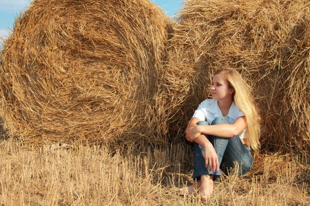young caucasian girl with golden hairs sits at bales of straw photo