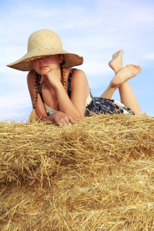 lolita: Young attractive barefoot girl in a hat above her eyes lying on a bale of yellow straw