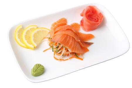 sashimi syake with slices of salmon, lemon lobules, ginger and wasabi on rectangular dish isolated on a white background photo